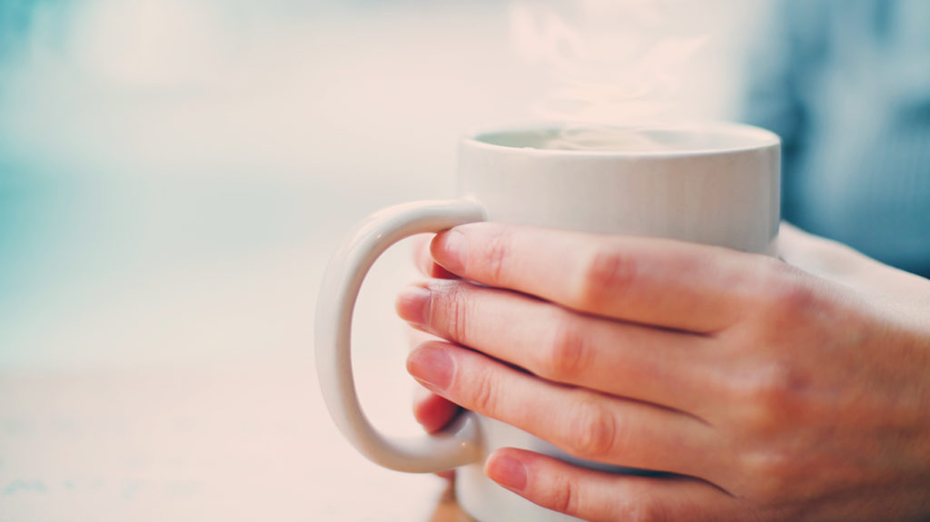 a person holding a mug of hot water that they are going to sip because that is how to stop a coughing attack