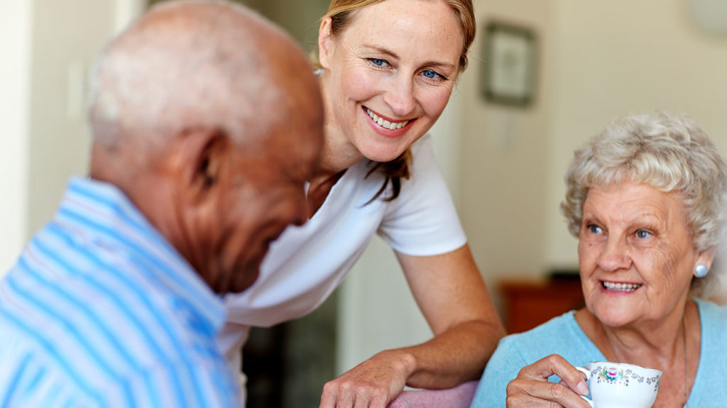 two seniors talking to a nurse about does medicare cover nursing homes
