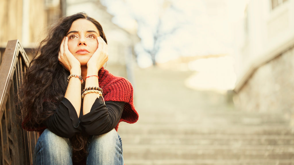 woman sat on the steps worrying about stress effects on the body