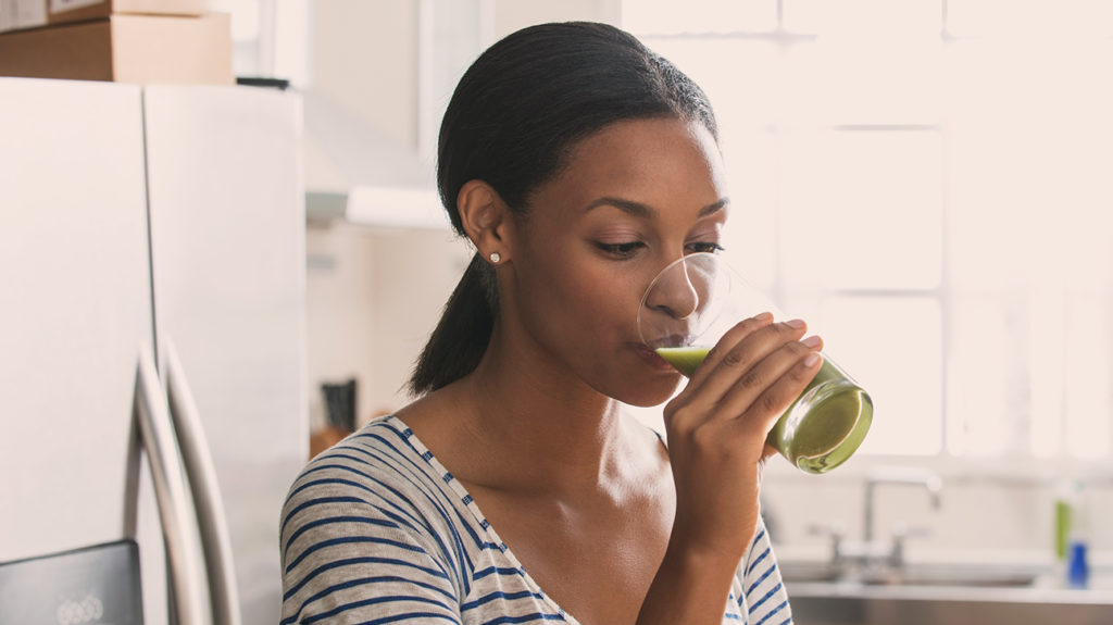 a woman drinking a green smoothie as part of her raw food diet