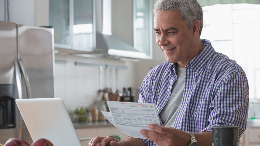 a man looking at medicare bills on paper and online to see what it will cost in 2020