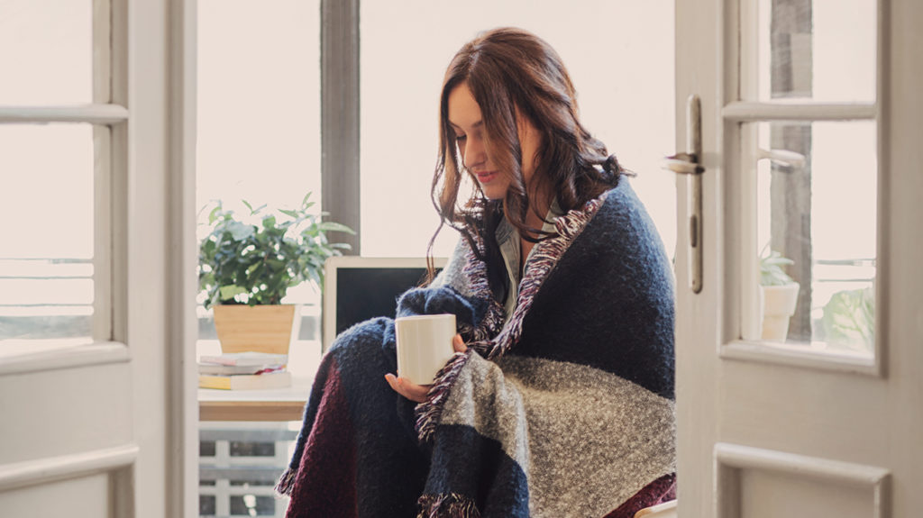 a woman wearing a blanket around her shoulders as she is experiencing the chills