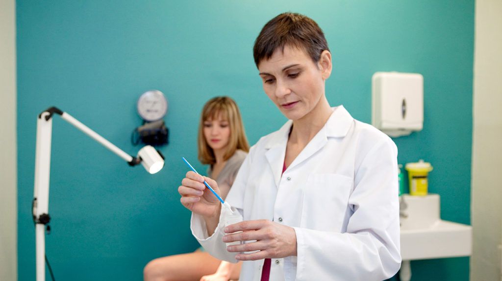 a doctor preparing a pap smear for a woman who is about the right age to have one