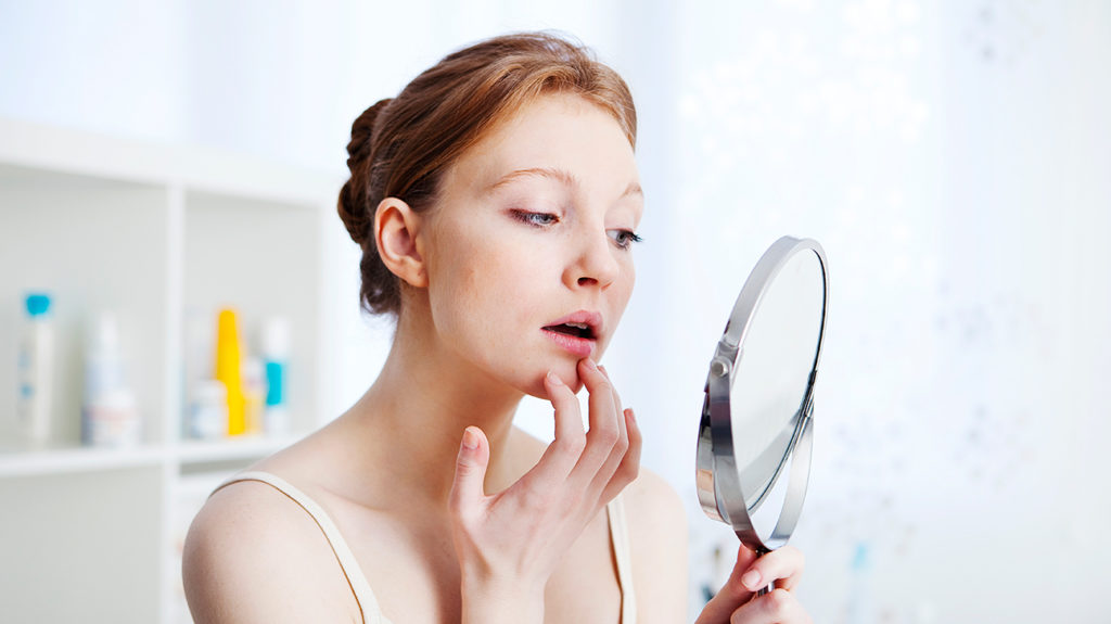 a woman looking in a mirror and inspecting a Blackhead on lip