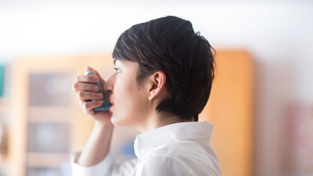 a woman using an asthma inhaler while indoors during a covid 19 lock down