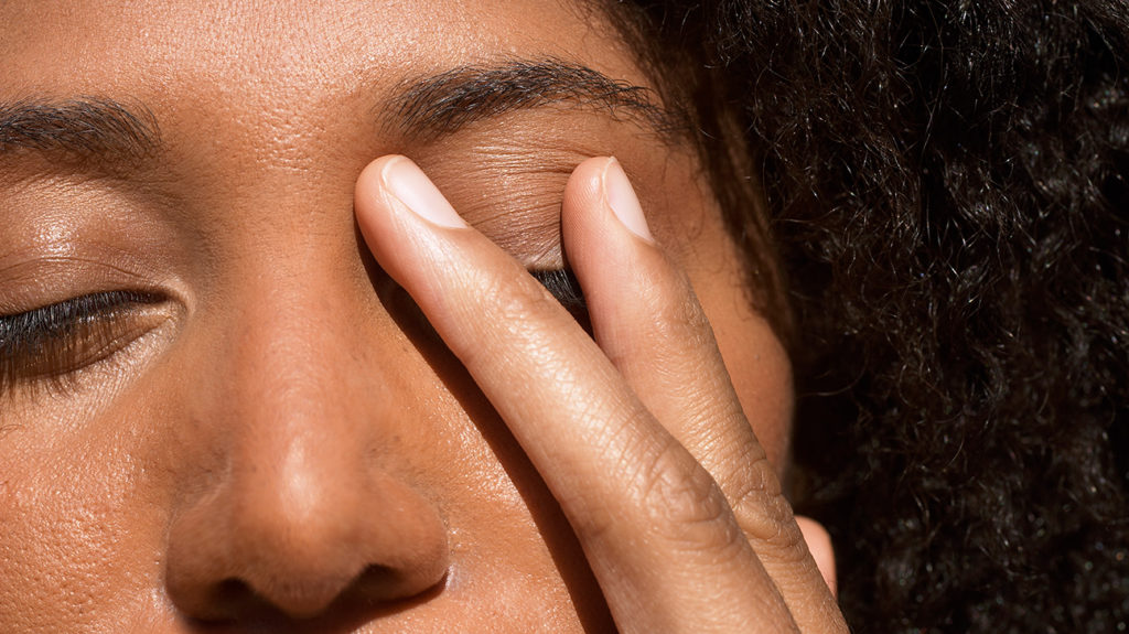 a woman holding her face because it feels like something is in the eye