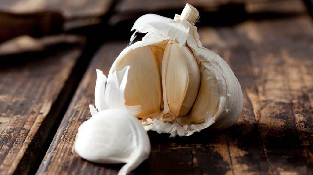 garlic, sat on a wooden table, which can be used to treat colds.