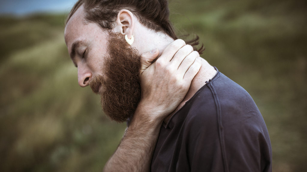 a man holding his neck because he has both a sore throat and neck pain