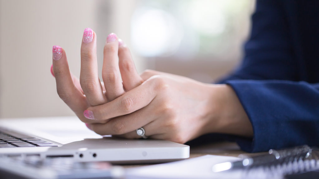 a woman holding her hand because she has pain there from inflammation