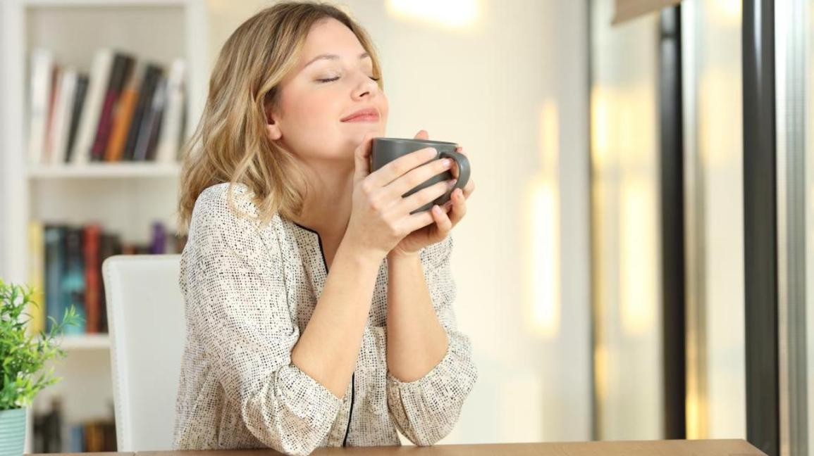 Woman looking relaxed drinking from a mug.