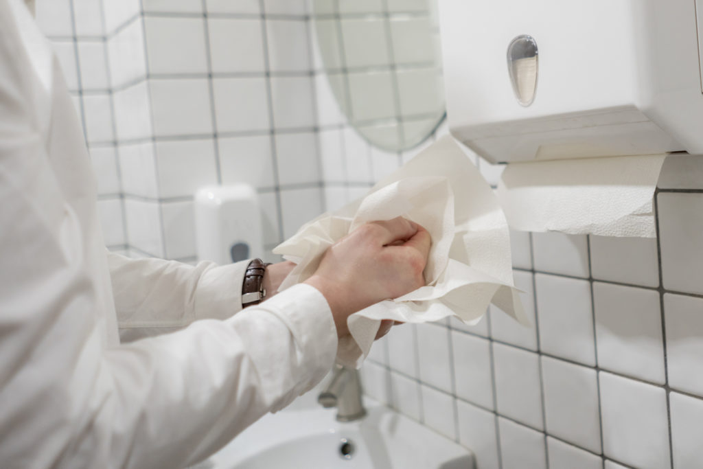 Man drying his hands with a paper towel