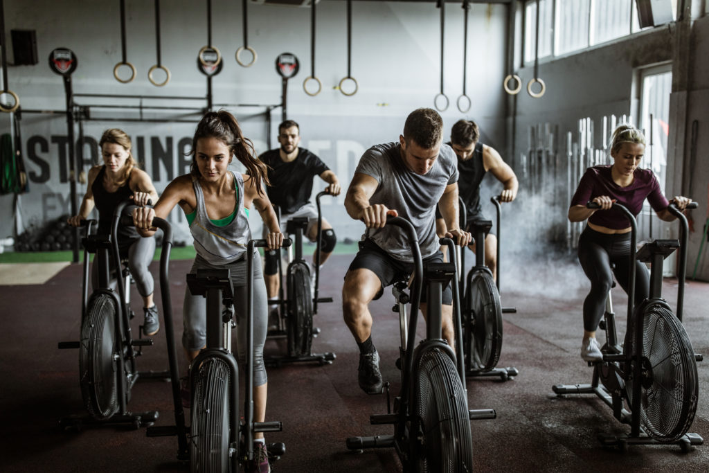 Homens e mulheres em bicicletas ergométricas