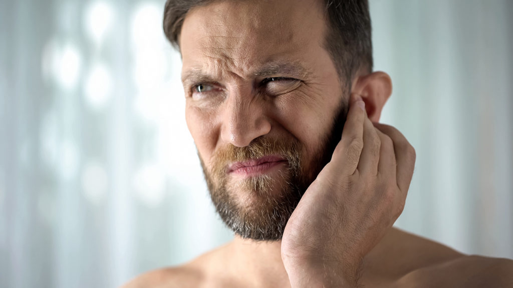 Man holding his ear due to clogged and ringing ears