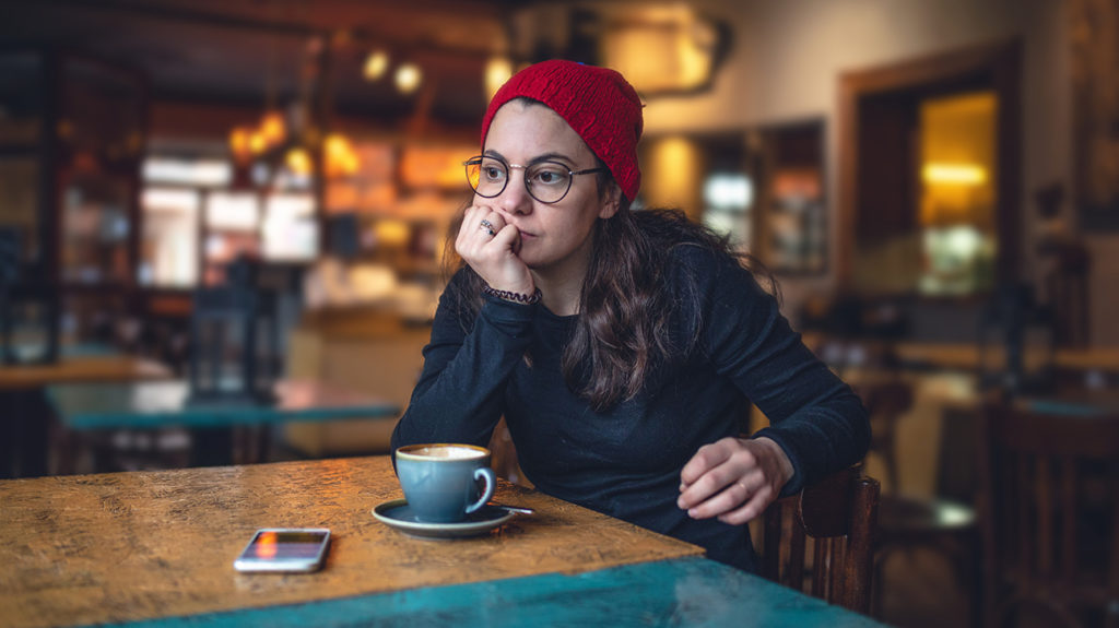 a woman sat in a cafe and looking slightly concerned because she is experiencing intrusive thoughts