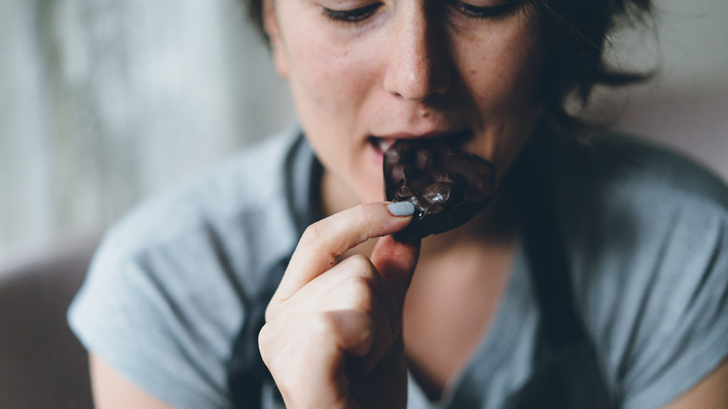 a woman eating chocolate where the sugar content may affect her depression