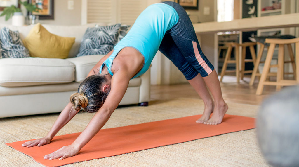 a woman doing downward facing dog to help with her Tight glutes