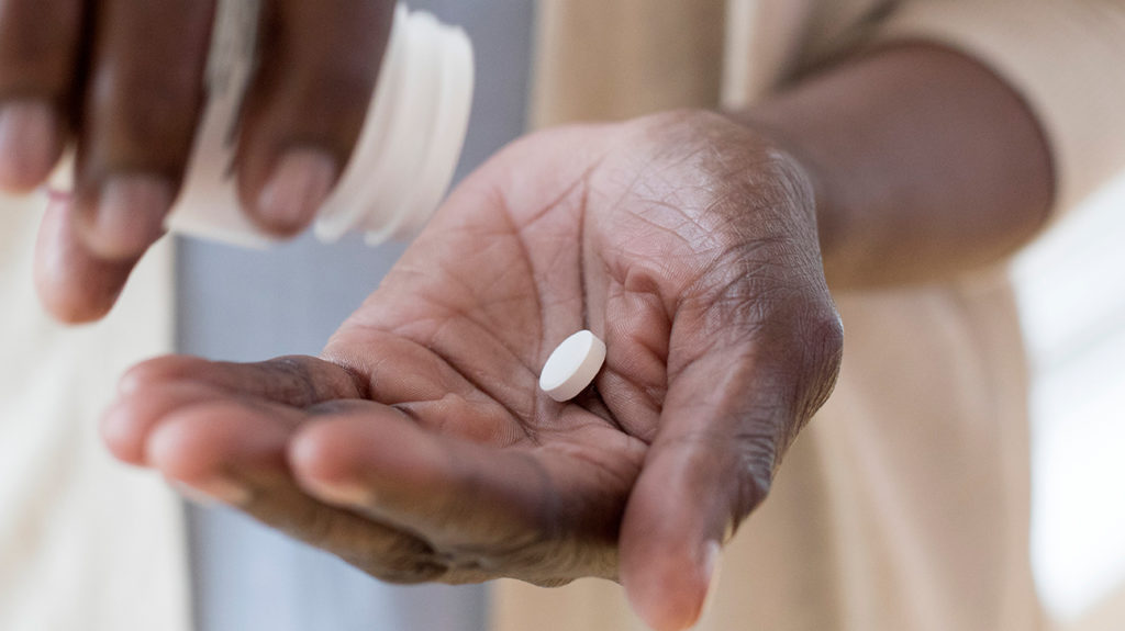 a woman pouring two pills into her hand that could act as medicines to fight COVID-19