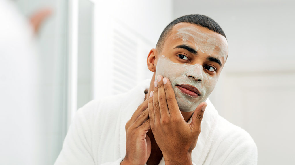 a man applying a facial to help treat his acne