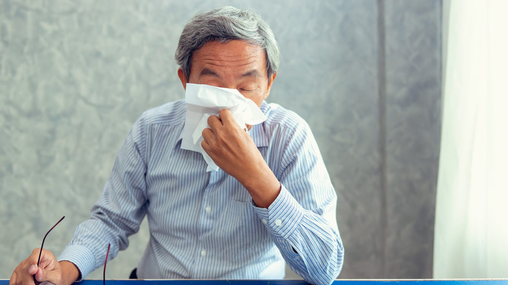 a man using a tissue to remove boogers from his nose