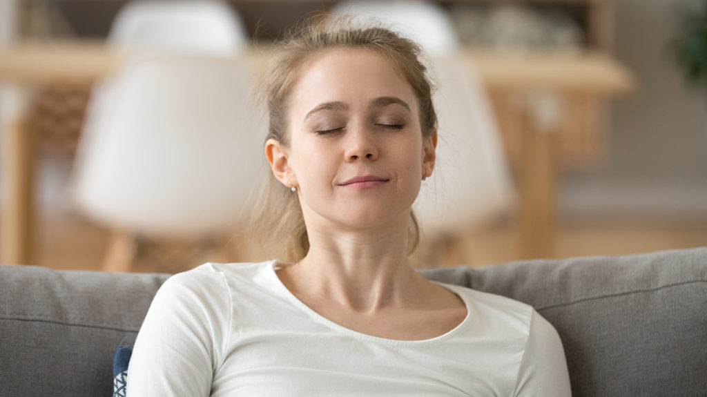 a woman taking a deep breath as she shows how to breathe properly