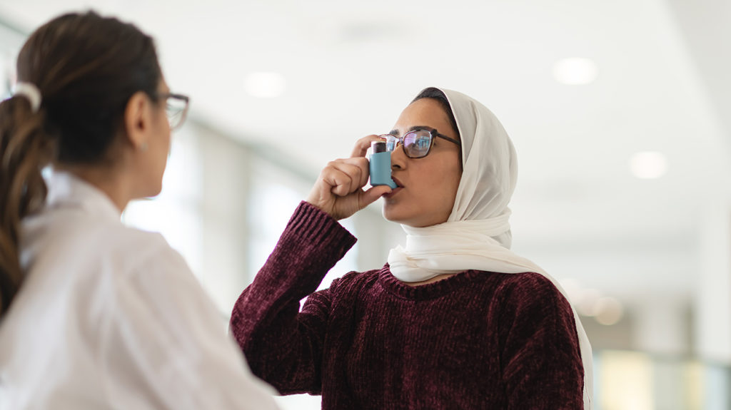 a woman using an inhaler to manage her asthma symptoms as it is not curable