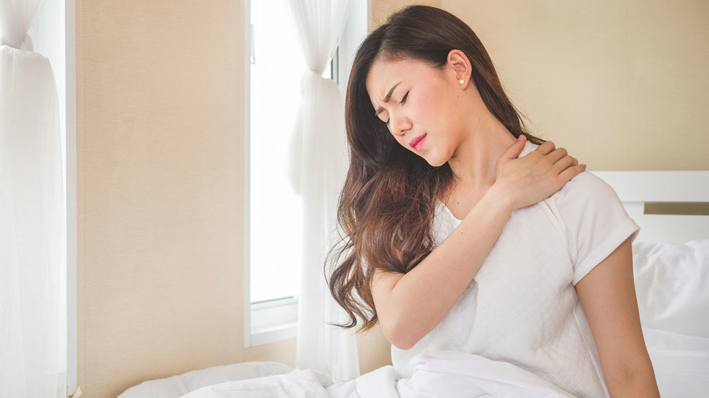 A woman wakes up with shoulder pain from sleeping.