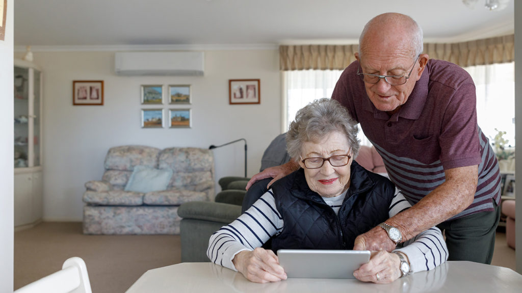 a senior couple on an ipad looking at information on medicare part b vs part d