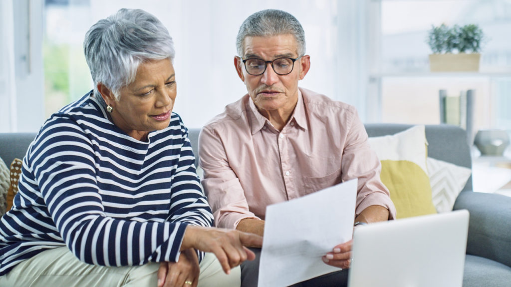 a senior couple looking a paperwork about Medicare Advantage vs. Medicare supplement plans