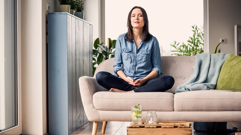 a woman practicing mindfulness at home as she believes it to be an effective natural treatment for blocked fallopian tubes