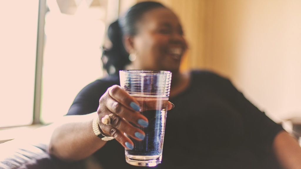 a woman holding a glass of water but what percentage of the human body is water