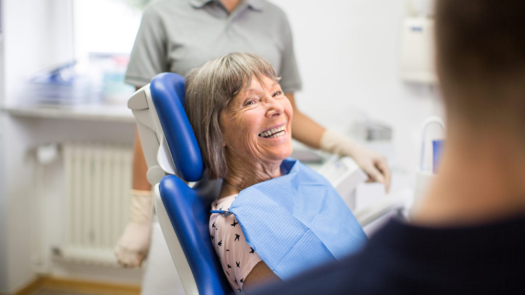 a senior woman at the dentist laughing about what are the advantages and disadvantages of medicare advantage plans