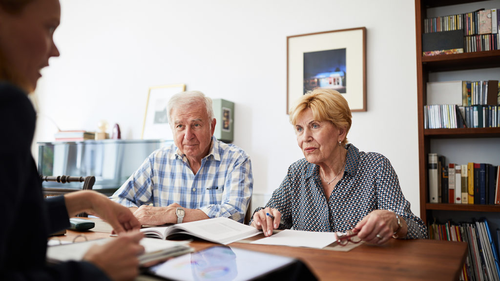 a senior couple talking to a medical advisor about the differences between medicare part a and b