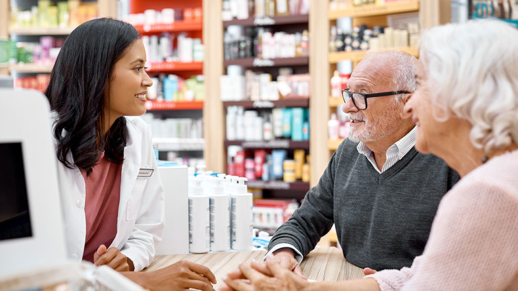 a senior couple talking to a pharmacist about medicare prescription plans