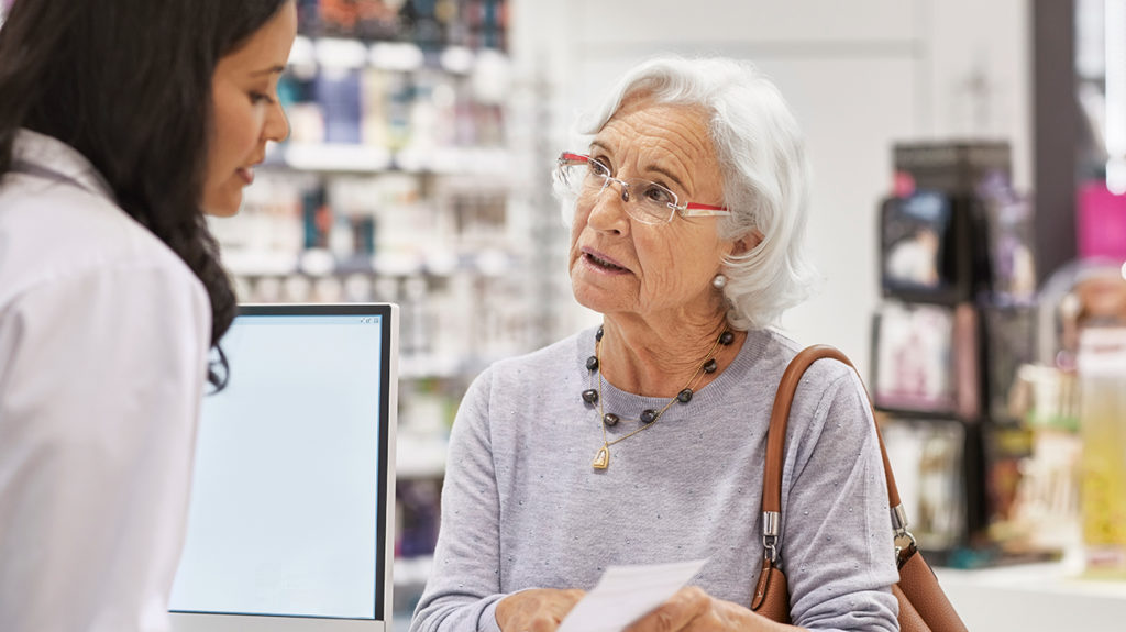 a woman in a pharmacy asking a member of staff if she has eligibility for free prescriptions with medicare part d