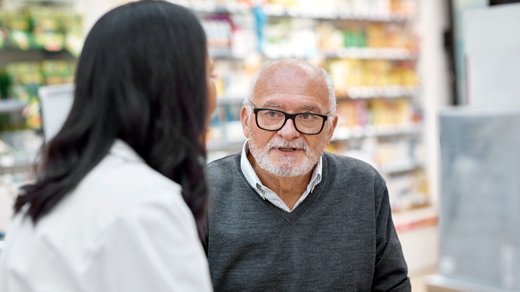a man talking to a pharmacist about medicare part d costs