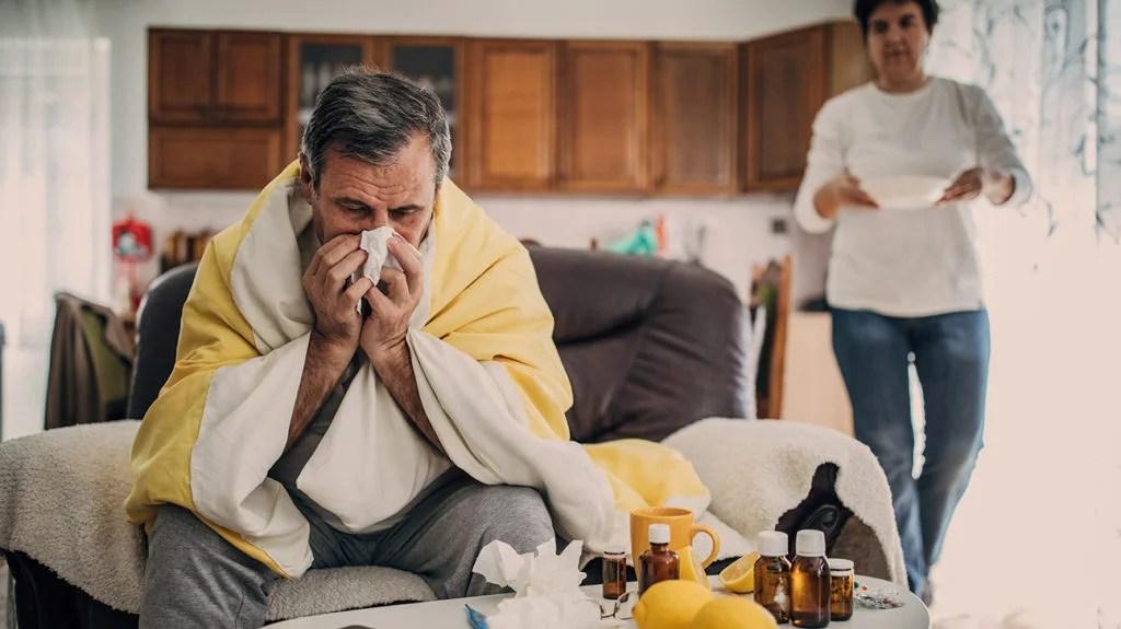 une femme portant de la nourriture à un homme malade et montrant comment prendre soin d'une personne grippée