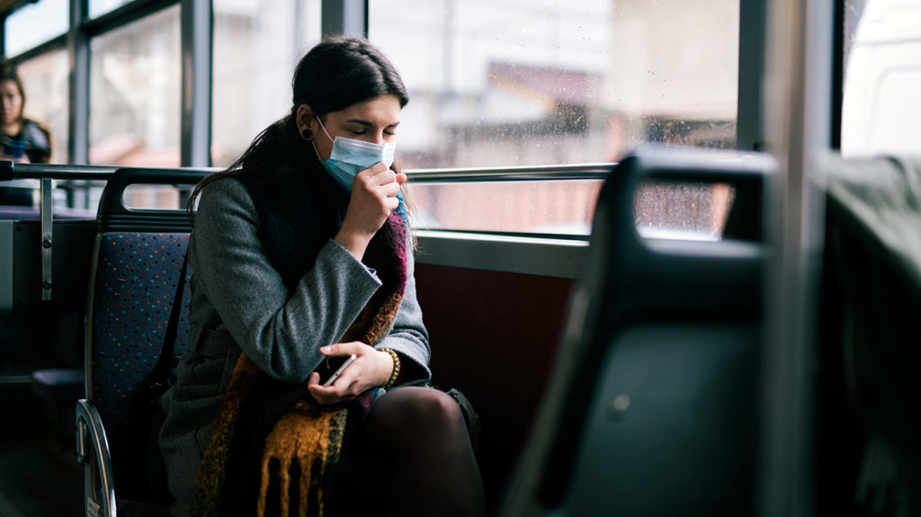 a woman on a bus sneezing. She is wearing a face mask in case coronavirus is airborne