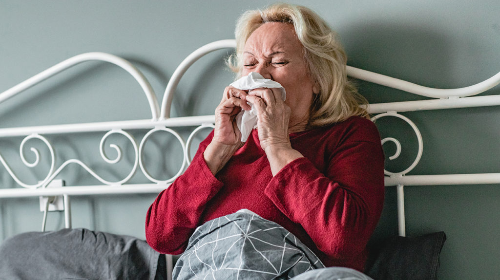 a woman experiencing pneumonia in bed because she has tested positive for COVID-19