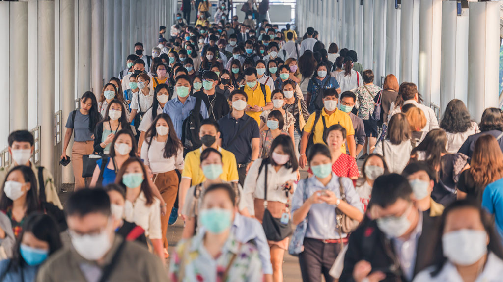 a crowd of people in Asia where a lot are wearing face masks to protect themselves from SARS