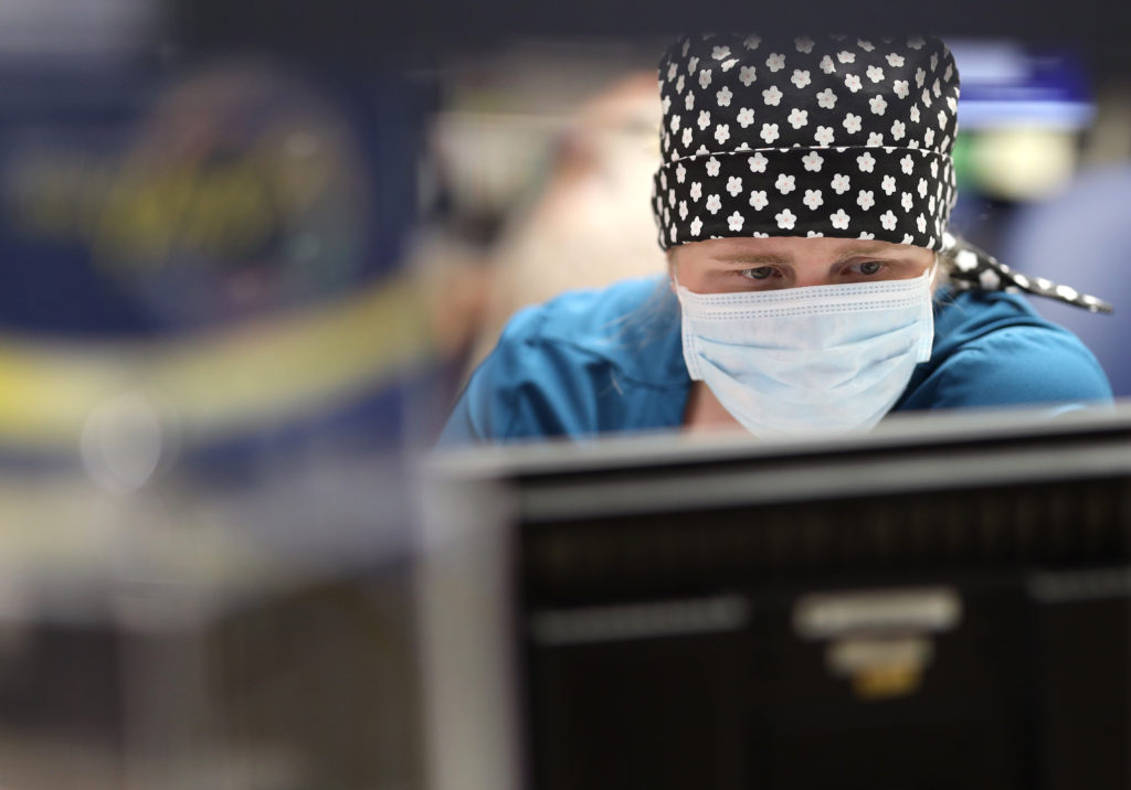 close up of a nurse's face wearing a face mask looking at a computer
