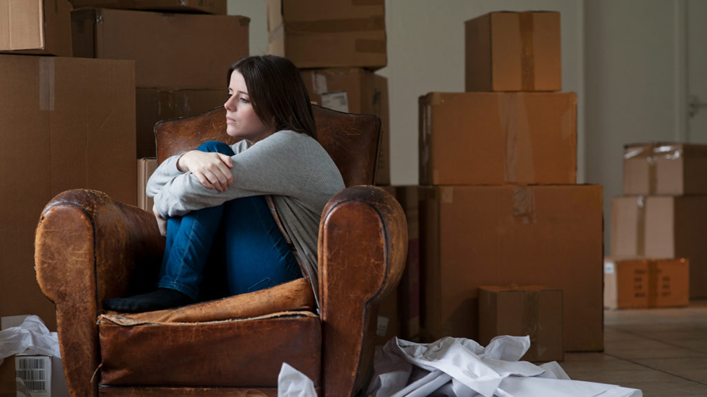 a woman looking sad sat amongst boxes as she has an adjustment disorder from moving house