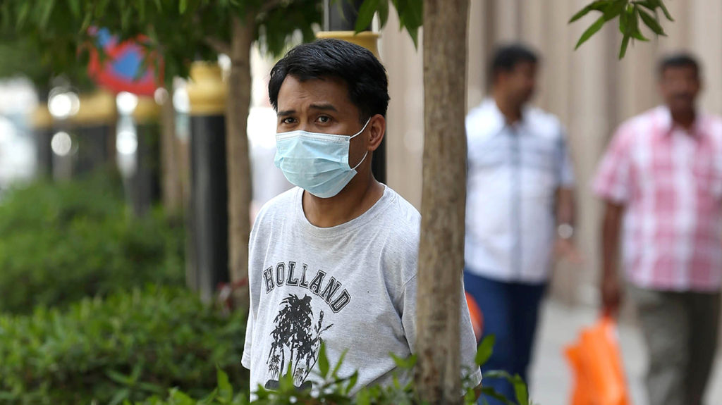 a man wearing a facemask to protect him from MERS-CoV