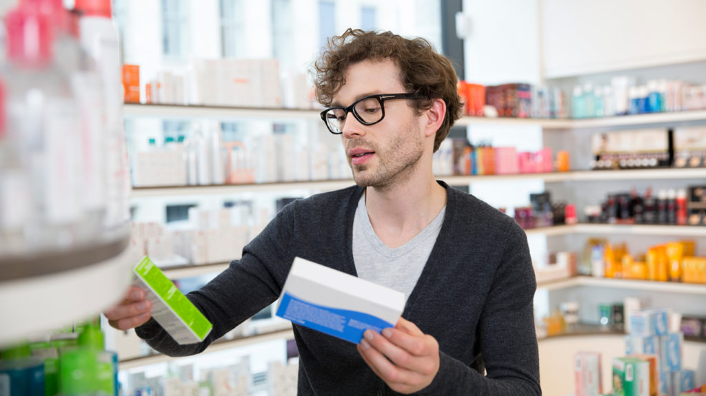a man shopping in a pharmacy looking for the best cold medicine