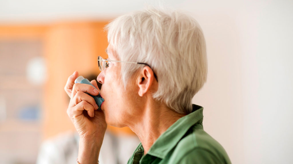a woman using an inhaler because she has one of the types of asthma