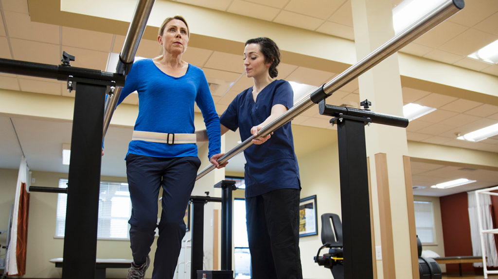 a woman having physical therapy as part of her spinal cord injury recovery plan