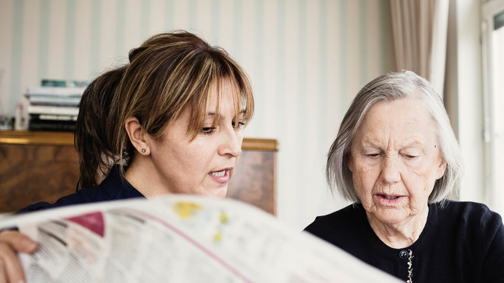 a woman reading a newspaper with a senior woman and showing how to care for someone with dementia