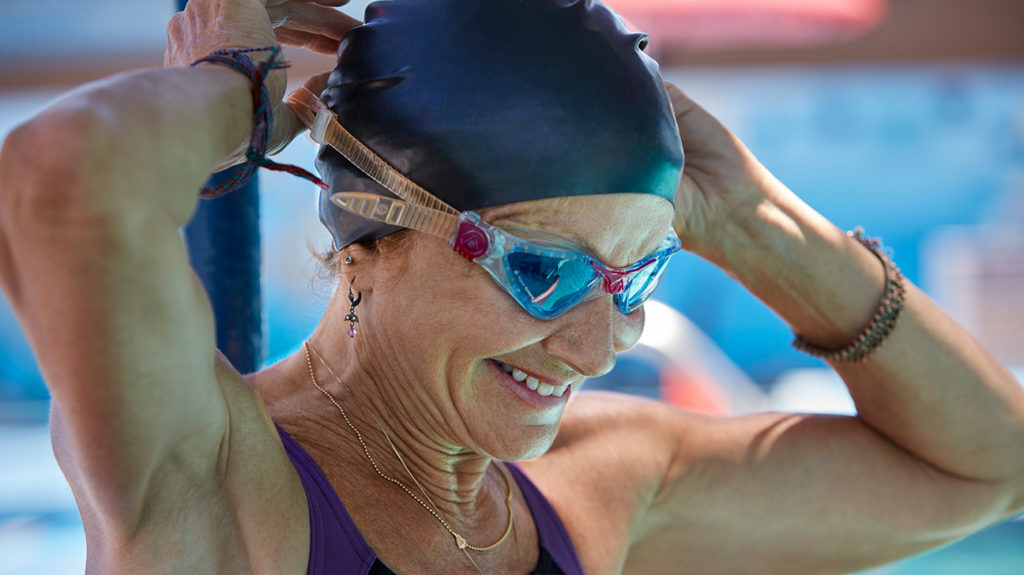 a senior woman adjusting her swimming goggles as she is about to go for a swin which is one of exercise that is safe for her hiatal hernia