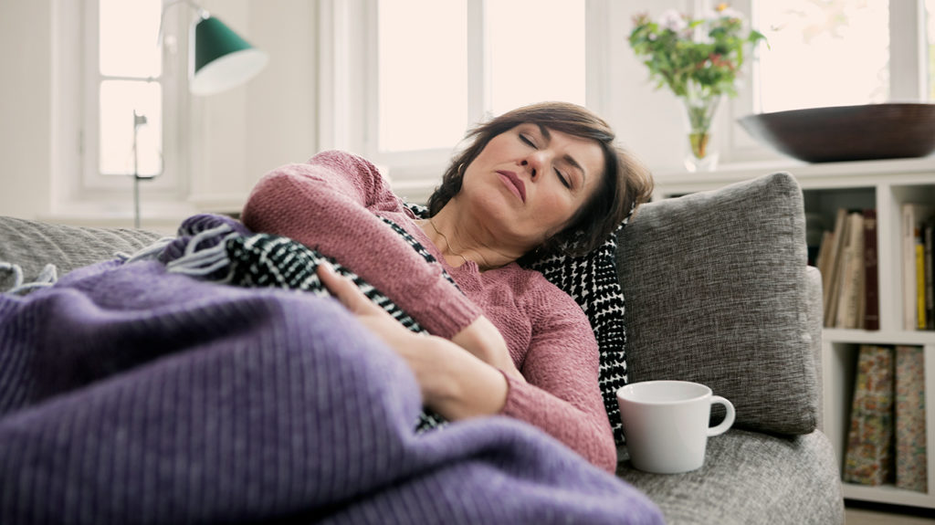 a woman sleeping on the couch because she has pneumonia