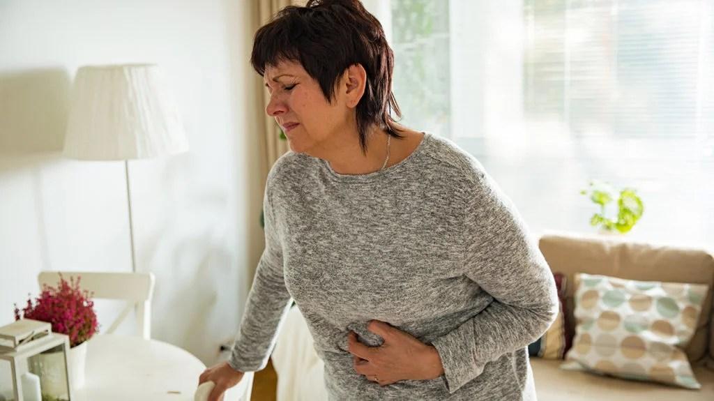 Crohns yüzünden mide ağrısı olan ve COVID-19 varsa semptomlarının daha kötü olup olmadığını merak eden bir kadın