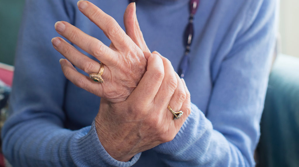 a woman holding her wrist as she has pain there from rheumatoid arthritis which might be made worse if she has covid 19